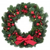 Christmas wreath with red bauble decorations and bow, holly, ivy, mistletoe, fir and pine cones over