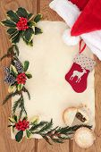 Christmas eve background border with red santa hat and stocking decoration, mince pie, holly, cedar