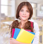 Portrait of cute teen girl standing in classroom with colorful books in hands, preparing to lesson,
