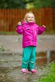 Happy little girl jumps into a puddle