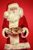 Santa Claus with Christmas treats, cookies. Over festive red background.