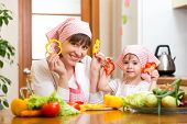 Woman And Daughter Cooking And Having Fun