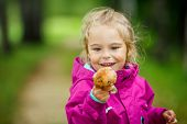 Season for mushrooms - little girl with a mushroom in the forest