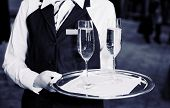Female waiter welcomes guests with champagne, toned image