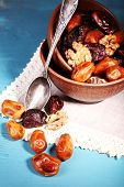 Tasty dates fruits in bowls, on blue wooden background