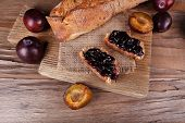 Bread with plum jam on wooden table close-up