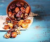 Tasty dates fruits in bowl, on blue wooden background