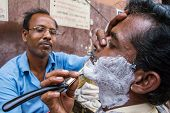 KOLKATA, INDIA - MARCH 13: Street barber shaving a man using an open razor blade on a street in Kolkata, West Bengal, India on March 13, 2013