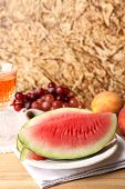 Composition of ripe watermelon, fruits, pink wine in glass  on  color wooden table, on color wall ba