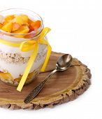 Healthy breakfast - yogurt with  fresh peach and muesli served in glass jar on wooden tray, isolated