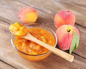 tasty peach jam with fresh peaches on wooden table