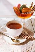 Cup of tea with macaroons on table, close up
