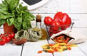Composition of colorful pasta, fresh tomatoes, basil, olive oil in bottle on wooden background