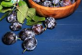 Ripe sweet plums in bowl, on wooden table