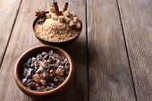Brown sugar cubes, reed and crystal sugar in bowls on wooden background