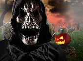 Grim reaper on graveyard, Halloween background.