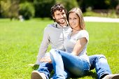 Young happy couple sitting in a park