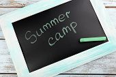 Text Summer camp written with chalk on chalkboard, close-up