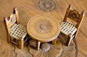 Mini Wooden Hand Made Chairs And Table On Carved Table