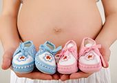 Close up on pregnant belly with pink and blue new born shoes.