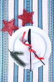 White plates, knife, fork, napkin and Christmas decoration on tablecloth