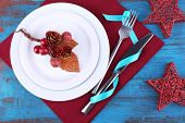 White plates, fork, knife and Christmas decoration on napkin on wooden background