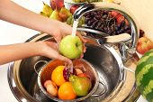 Woman's hands washing apple and other fruits in colander in sink
