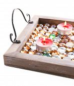 Candles on vintage tray with decorative stones, isolated on white