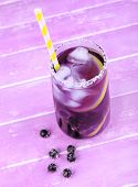 Glass of cold berry cocktail on wooden background