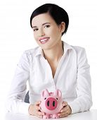 Happy businesswoman holding piggy bank.