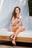 Beautiful young woman at the summer lounge with white champagne glass