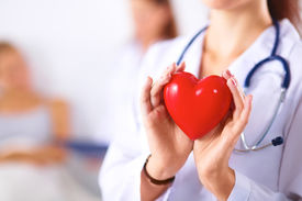 stock photo of beating-heart  - Young woman doctor holding a red heart - JPG