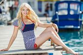 picture of flowing hair  - Beautiful blonde with blue eyes and long flowing hair, earrings in your ears, on the neck is a chain with a pendant, wearing a striped short dress walks on the pier, near the yacht club, on the arm is a bracelet. ** Note: Visible grain at 100%, best at s - JPG