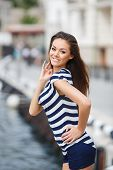 Portrait of a gorgeous brunette posing near the yacht club.
