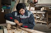 image of carpentry  - Young craftsman in uniform working at carpentry - JPG