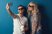 Lovely Couple young man and woman girl in sunglasses Taking Selfie with attractive smiles