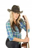 stock photo of cowgirl  - a cowgirl with a serious expression on her face holding on to her guitar - JPG