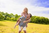 Portrait Of Happy Caucasian Couple Playing Outdoors In Summer. Having Fun While Piggybacking And Hap
