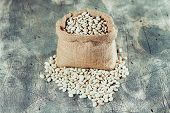 stock photo of phaseolus  - Sack with white beans on wooden table - JPG