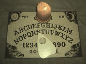 stock photo of ouija  - This is a Ouija board with lit candle on the antique setting - JPG