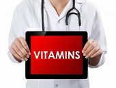 Doctor Showing Tablet With Vitamins Text.