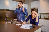 image of angry man  - Angry young man arguing at phone while a woman calculating their bank credit lines. Financial family problems concept.