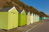 Green beach huts in a row with blue sky traditional English structure and shelter