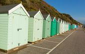Light green beach huts in a row with blue sky traditional English structure and seaside shelter