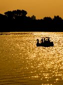 picture of pedal  - silhouette couple in swan pedal boat on sunset at parkThailand - JPG