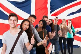 picture of stand up  - Group Of Happy Multi Ethnic Students Standing In Front Of Uk Flag Showing Thumb Up - JPG