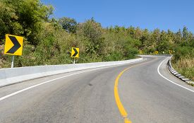 pic of safety barrier  - Forest road with barrier and warning curve road sign - JPG
