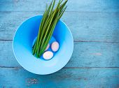 pic of dingy  - Natural white eggs in a blue bowl and Spring onions over dingy  blue wooden table - JPG