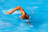 stock photo of crawling  - young man swim crawl style in outdoor swimming pool - JPG