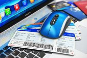 stock photo of boarding pass  - Wireless computer PC mouse and stack of airline boarding pass credit cards and passports on laptop or notebook keyboard with selective focus effect - JPG